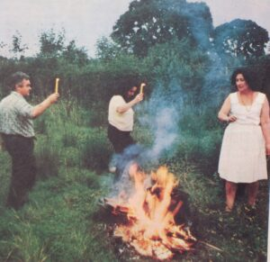 Eleanor Bone, a woman, and Bill Bone dancing around a fire in a field, while holding a candle.